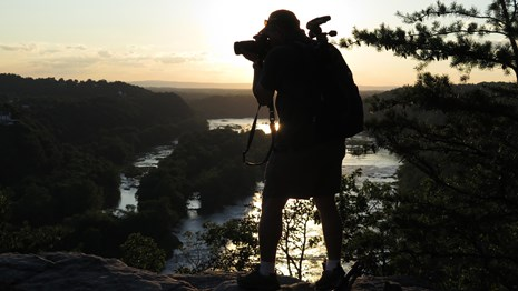 silhouette of a man taking a photograph; backdrop is trees, sky at sunset, and the river below