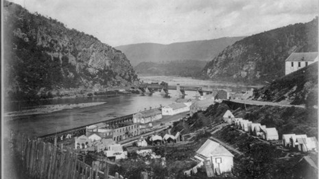 1860s black and white photo of Harper Ferry showing the mountains, gap, former armory grounds, etc.