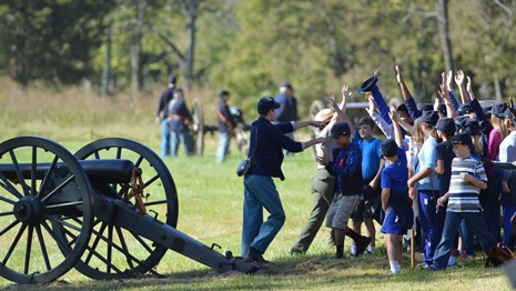 kids with hands raised next to a ranger, a volunteer dressed as a Civil War soldier, and a cannon