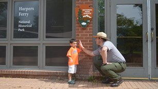 park ranger and young boy high five in front of the park visitor center
