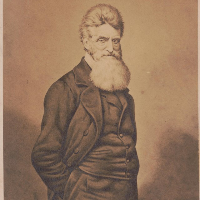 image of John Brown, wearing a vest and long coat, standing with his hands in his pants' pockets