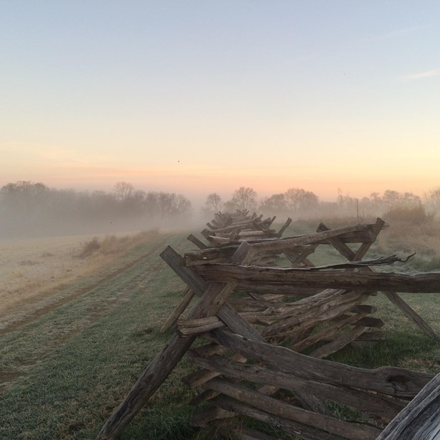 misty morning; colors from the sunrise in the distance; fence on the battlefield in the foreground