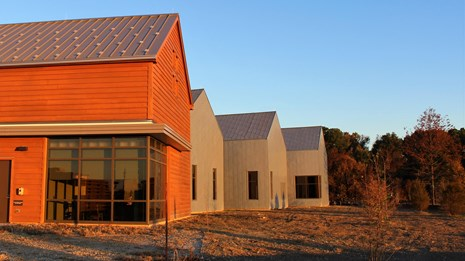 Sunrise reflecting on the exterior of a brown and gray visitor center