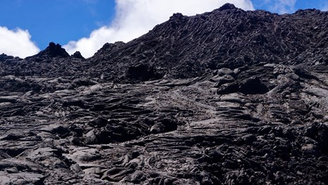 A cooled lava flow under blue sky