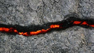 A crack in rock with molten lava shining through