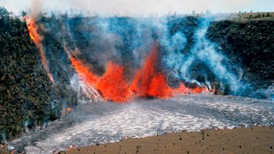 An erupting volcanic fissure at the base of a pit crater fountains orange molten lava and pools it