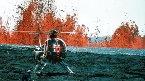 Helicopter on the ground in front fountains of orange molten lava