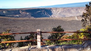 Overlook into a volcanic crater with trees in the foreground