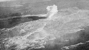 Black and white aerial photo of a bomb exploding on a lava flow