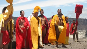 Hawaiian aliʻi and attendants all wearing red and yellow on the edge of a volcanic crater