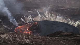 A lava lake in a volcanic crater, with half of it black and stagnant and the other half glowing