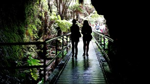 Silhouetted human figures at the entrance to a lava tube