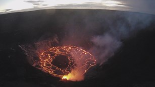 Web cam image of an erupting volcanic crater, with pooling lava in the bottom