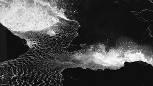 Black and white photo of molten lava at night, from above.
