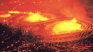 Glowing orange molten lava lake from above.