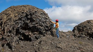 A person standing next to a large lava formation