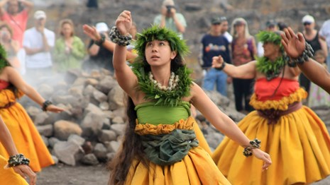 A hula dancer in a yellow skirt