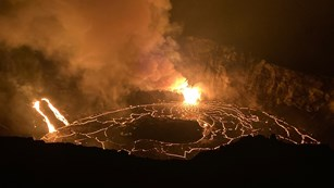 Erupting volcanic crater glowing at night