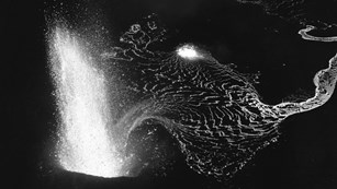 Black and white photo of a lava fountain from above at night