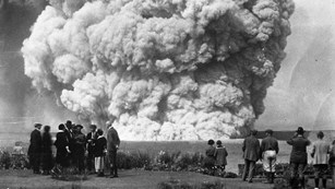 Black and white photograph of human figures in front of an ash cloud