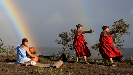 A kumu with drum and hula dances on the rim of a volcanic caldera