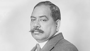 Black and white photograph of a sitting man with a mustache