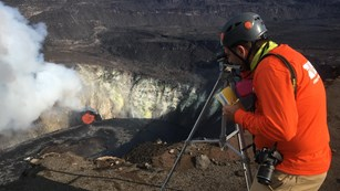 Scientist using a monitoring device atop the edge of a lava lake in a volcanic crater