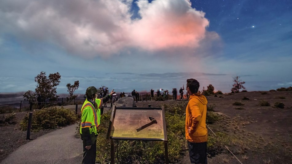 Park visitors watching a volcanic eruption from an overlook with a stone wall