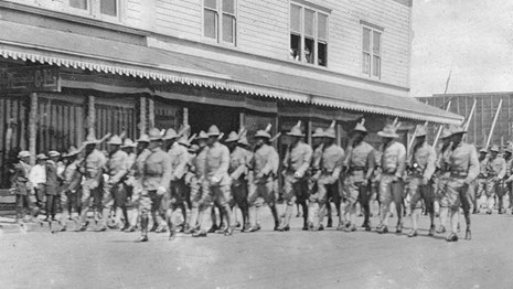 Black and white photo of a company of soldiers marching through a town street