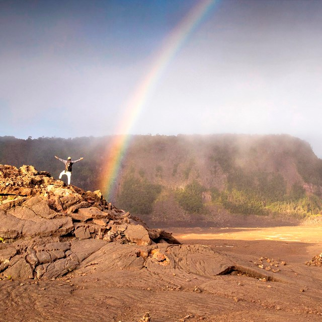 Rainbow inside a crater with a hiker in the foreground