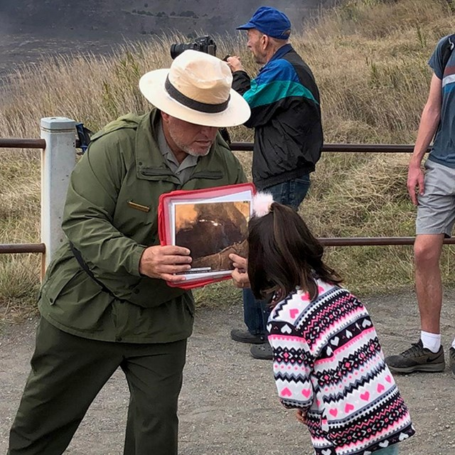 A park ranger holds a photo up to a pointing child