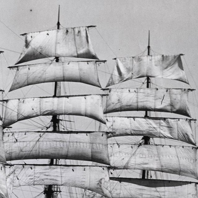 B&W photo of ships mast with sails