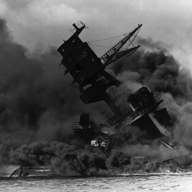 B&W photo of sinking ship surrounded by smoke