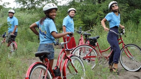Young adults standing with red bikes and wearing helmets
