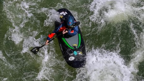 kayaker in white and green waters of river rapid as seen from above on a bridge