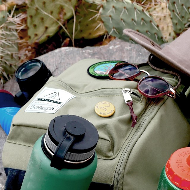 Water bottles, backpack, hat, and sunglasses