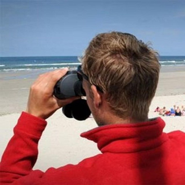 One male life guard looking through binoculars and the other male lifeguard holding radio