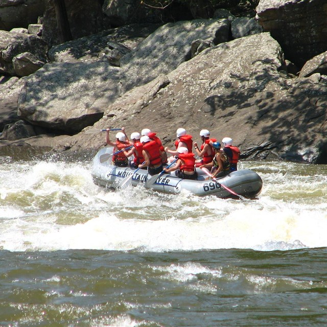 Group of paddlers wearing helmets and life jackets in inflatable raft on river
