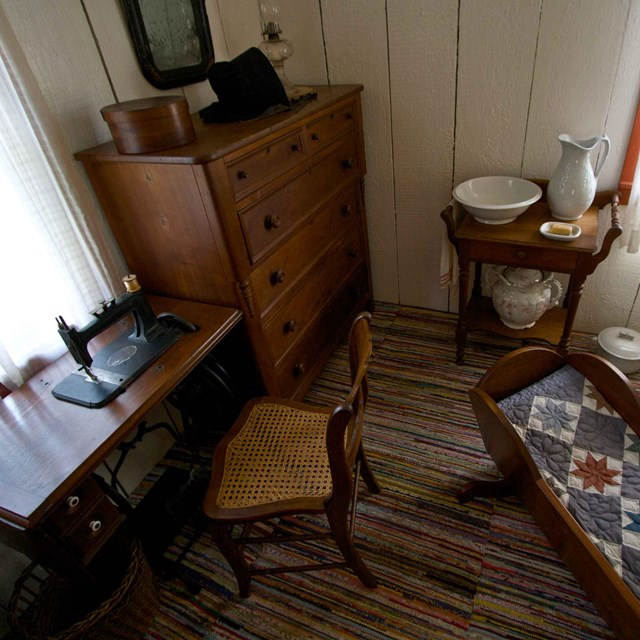 A small room is furnish with an antique bureau, sewing machine, and cradle.