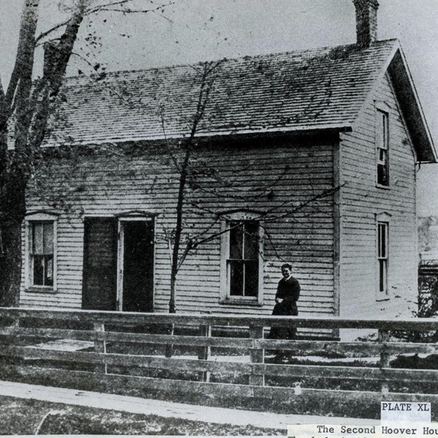 A woman poses in front of a two story frame house with two maples in the front.
