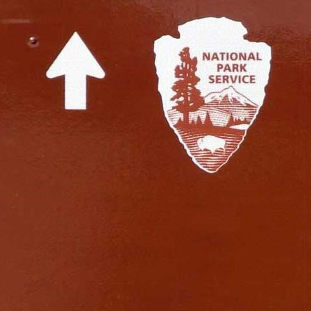 A brown road sign gives directions to places at Herbert Hoover National Historic Site.