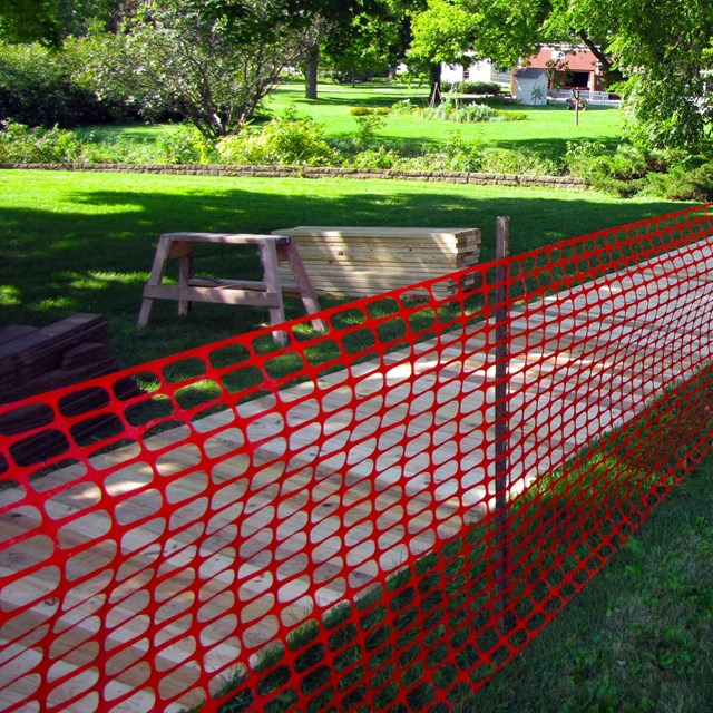 A orange fence closes a wooden sidewalk during repairs.