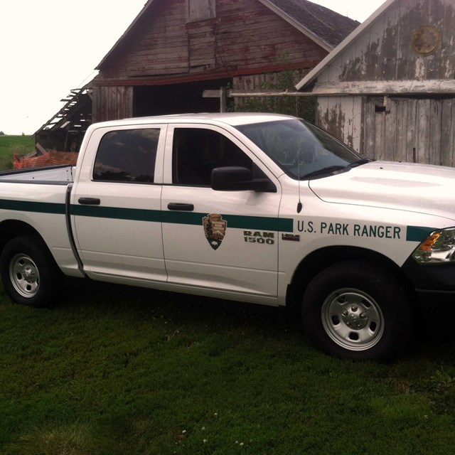 A park ranger patrol truck, painted white with a green stripe, is parked by a barn.