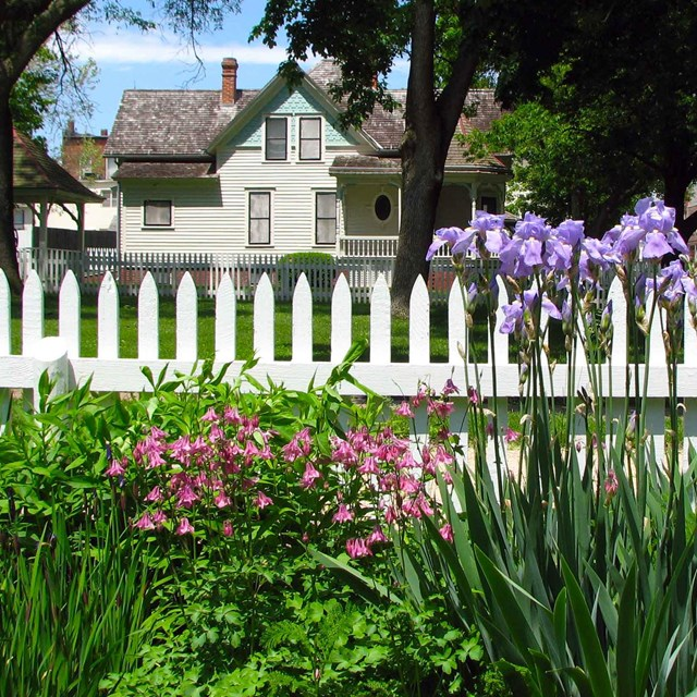 A white picket fence separates purple flowers from a white house.