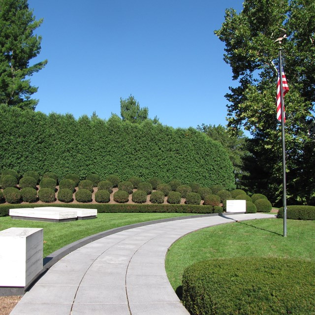 Two plain marble ledgers mark graves in a semicircular planting of shrubs with a US flag.