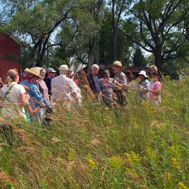 A park ranger addresses a group of visitors by a barn in a prairie.