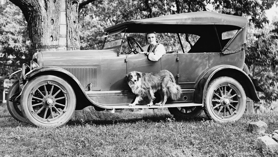 Black and white picture of woman in driver's seat of 1920s car with a dog. Library of Congress photo