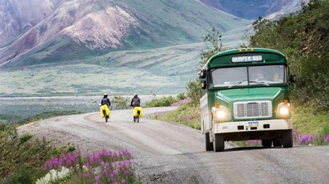 green bus past two bikers headed towards mountains