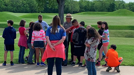 A group of students listen to a ranger on a patio in front of green grass and mounds