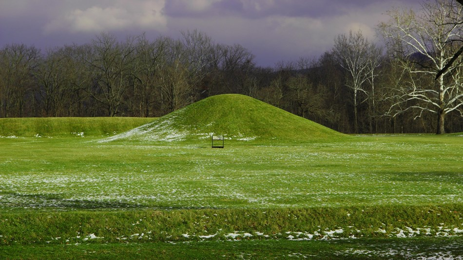 A large grass-covered mound under a dark grey sky